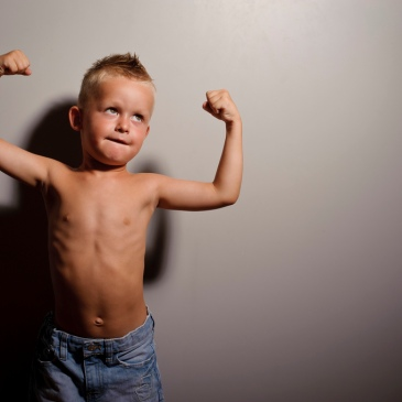 Young boy flexing muscles
